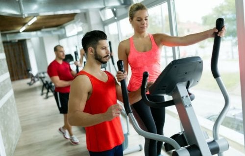 woman on elliptical at gym with trainer slimming down with cardio