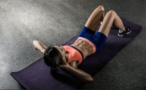 woman doing crunches on mat empty room ripped abs fast