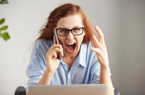 kvinde der sidder foran computer og råber mens hun taler i mobil