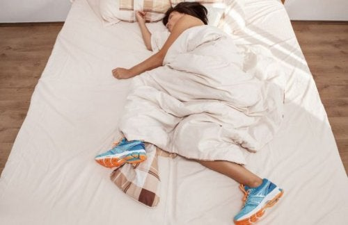 woman sleeping in bed with running shoes