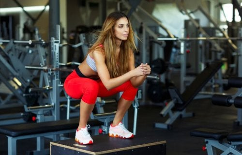 woman doing squat jump at gym CrossFit
