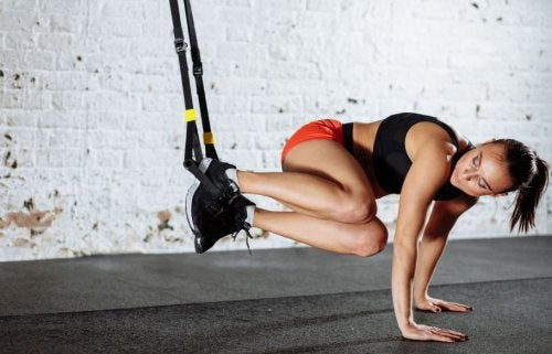 woman using TRX bands at the gym