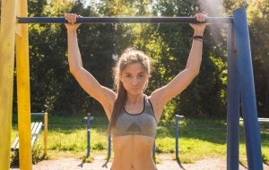 Woman working out with pullup bar equipment.