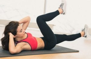 Woman doing bicycle crunches to reduce belly fat.