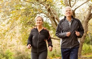 Way to age better: A couple running in the woods.