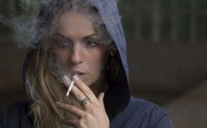 Woman smoking with her hood on.