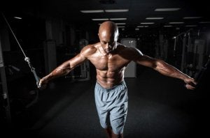 Man using a pulley machine as part of this routine to tone your chest.