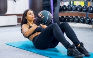 Woman doing sit ups with a medicine ball.