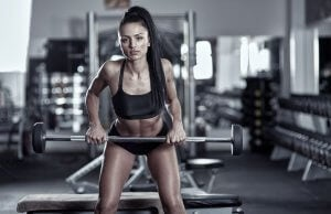 Woman doing Barbell Row in the gym.