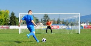 Soccer player scoring a goal.