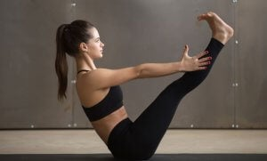 Woman doing the navasana yoga pose.