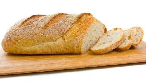 skærebræt med et lyst, halvt skiveskåret franskbrød