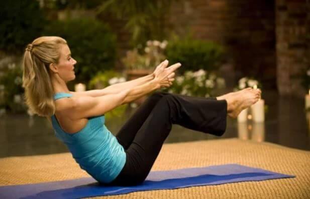 kvinde i en yogastilling på en måtte
