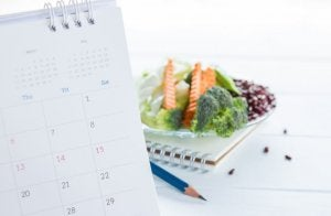 A calendar to plan a healthy diet and a plate with healthy food.