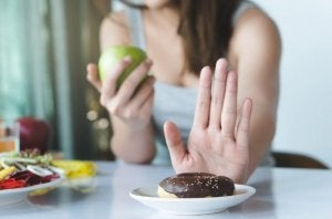 Woman rejecting unhealthy foods and eating a piece of fruit instead.