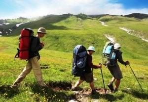 Three men carrying their trekking backpacks.