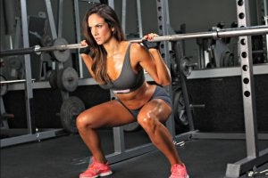 Woman doing squats in the gym. She can see results.