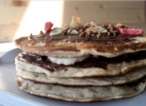 stack of pancakes with chocolate syrup and bananas
