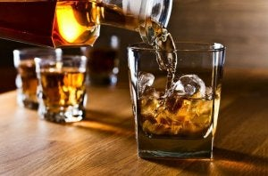 Bottle pouring whiskey in a glass.