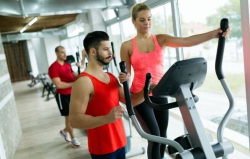 woman at gym with trainer benefits of elliptical machines