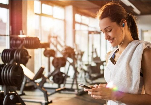 woman smiling looking at phone at the gym
