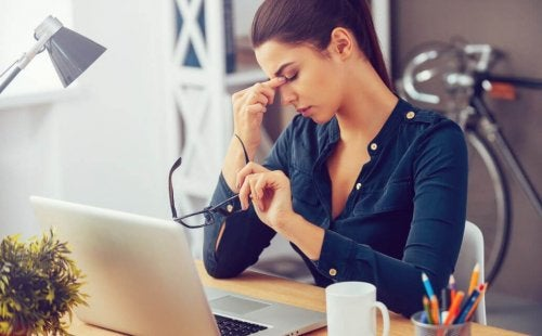woman rubbing her eyes at work thinking about the psychological aspect of weight loss