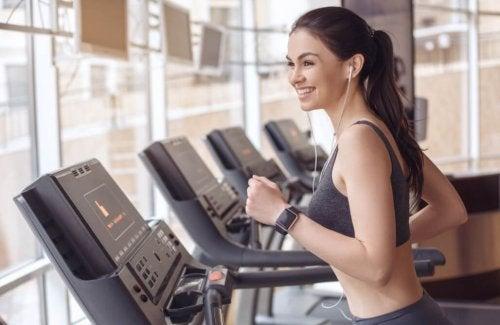 glad kvinde på løbebånd med musik i ørerne