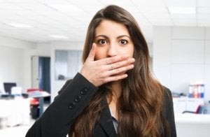 Woman covering her mouth because of Halitosis