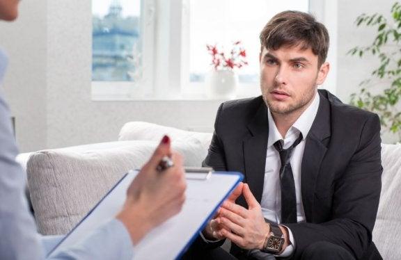 Mand i jakkesæt til en samtale hvor der tages noter