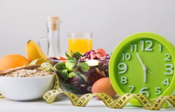målebånd, mad og ur der ligger på et bord