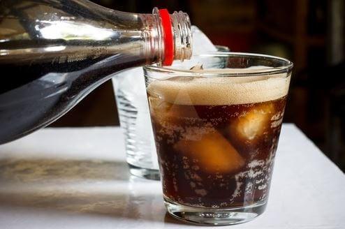 cola der hældes over i glas med isterninger