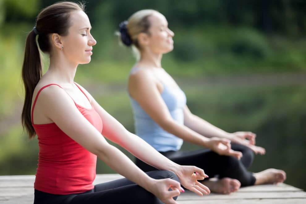 Two women meditating practice yoga every day