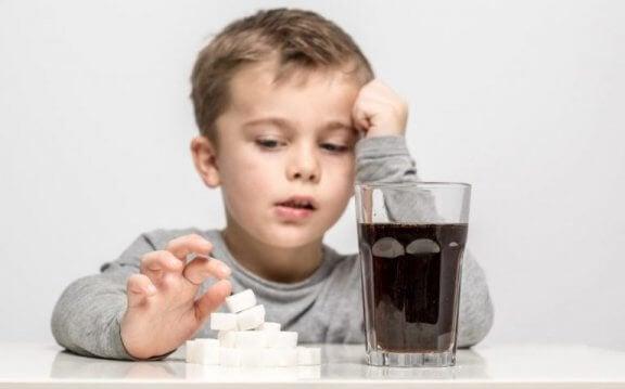 lille dreng der sidder med sukkerknalder og et stort glas cola