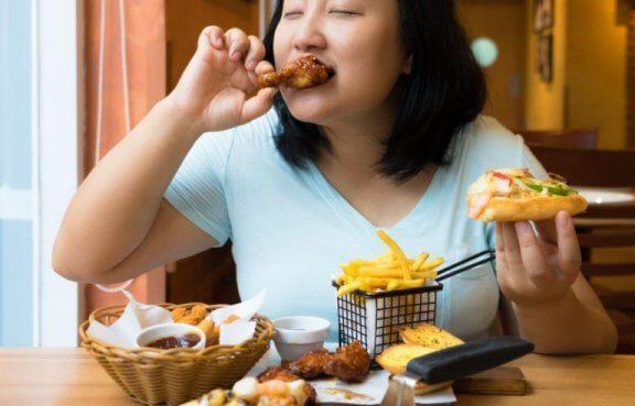 kvinde der spiser et stort måltid junkfood