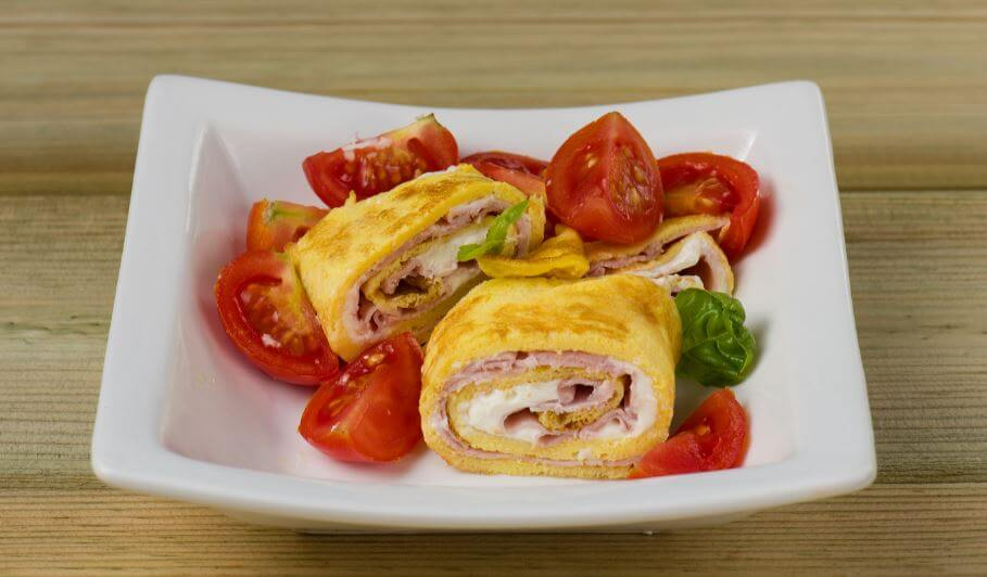 Ham and cheese rolled potato omelette with tomato garnish