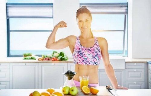 veltrænet kvinde der flexer i sit køkken