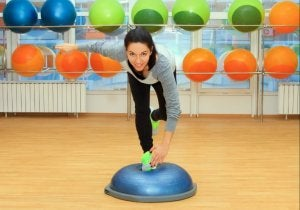Psychological benefits of exercising, woman working out with bosu ball.