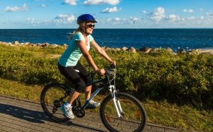Woman goes cycling by the sea.