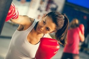 Woman fighting depression by punching heavy bag.