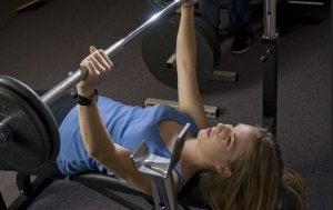 Exercises: woman doing bench press.