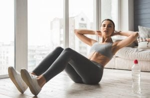 Exercises: woman doing abs at home.