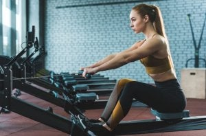Girl building her back with rowing machine.