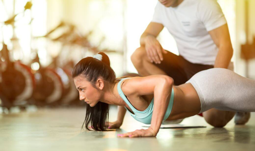 Personal trainer and woman doing push-ups.