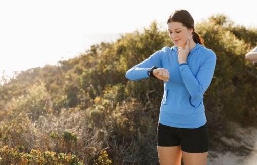 kvinde der måler sin puls og kigger på sit pulsur
