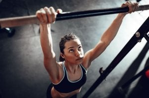 Woman trying to do pull-ups.