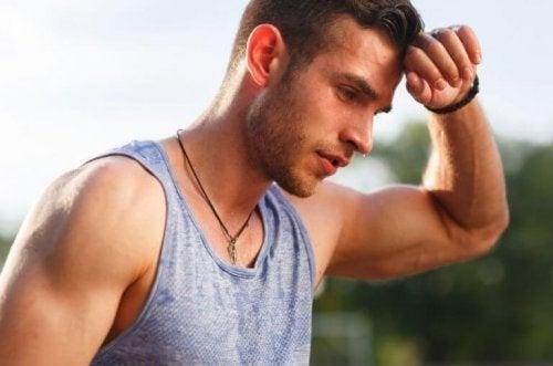 Man gray shirt wiping sweat