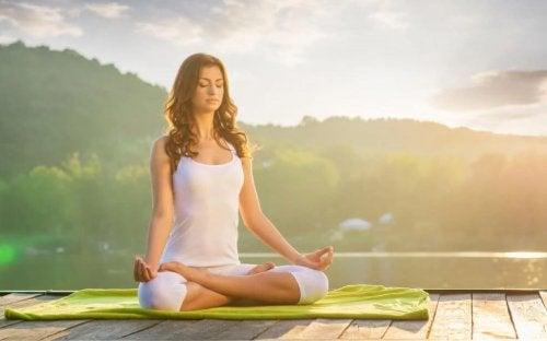 Ways to reduce stress woman sitting on dock on lake meditating
