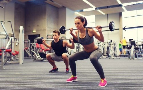 Woman and man strength training with squats.