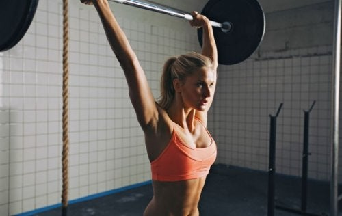 Woman strength training with a military press.