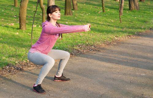 kvinde der laver squat udenfor på en sti